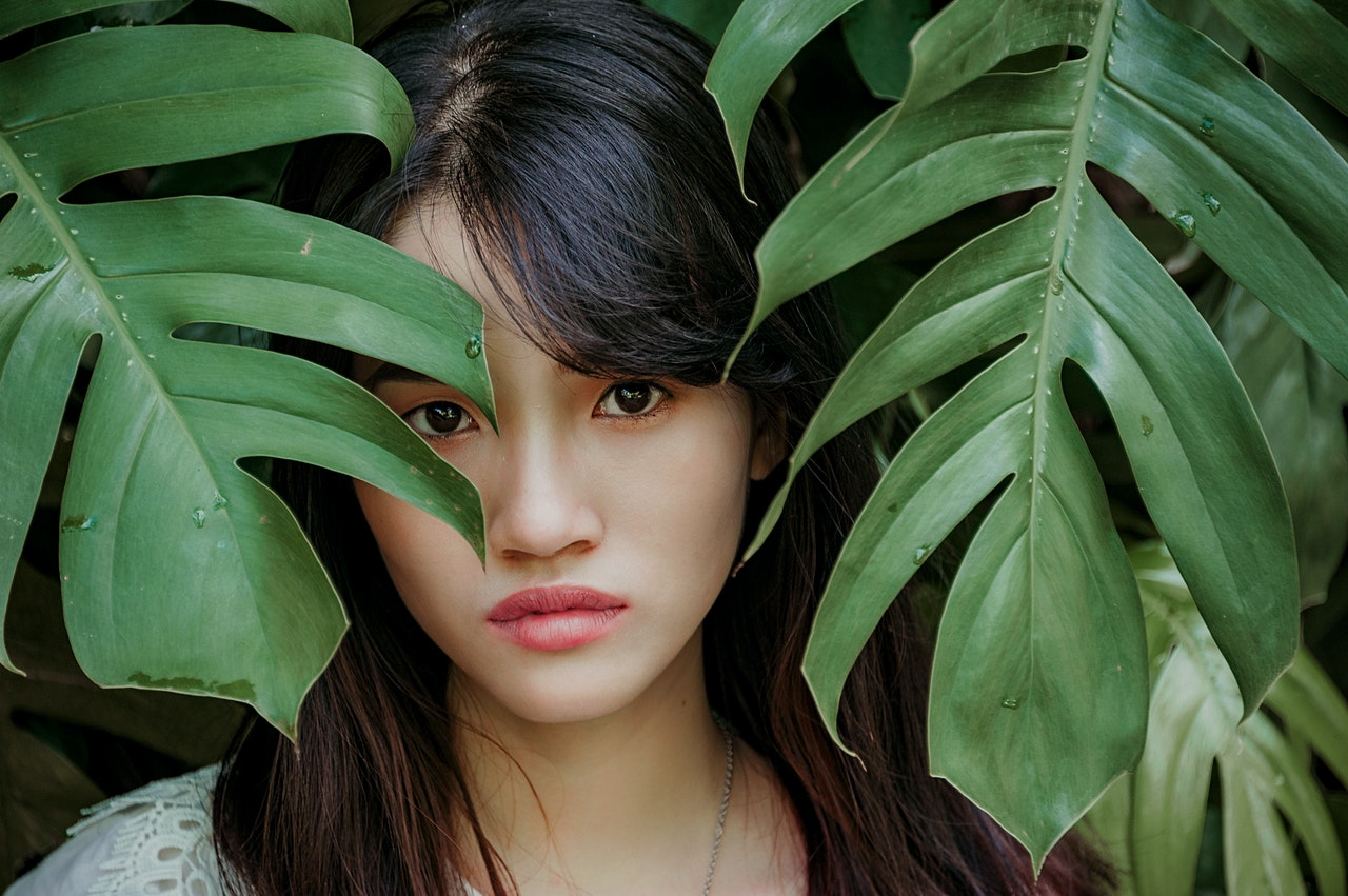 Philippine woman standing between green leafed plant